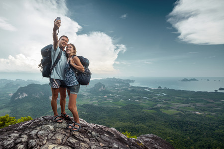 Foto de Two hikers taking selfie on top of the mountain - Imagen libre de derechos