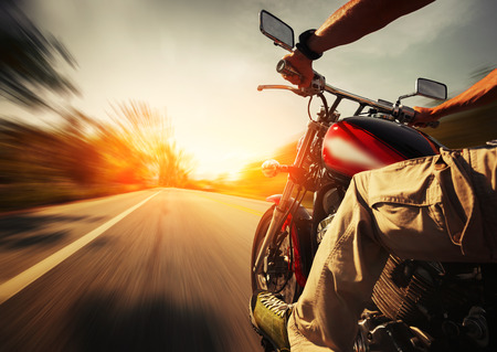 Foto de Biker riding motorcycle  on an empty road at sunny day - Imagen libre de derechos
