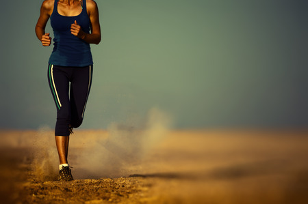 Photo pour Young lady running in the desert. Edges are blurred focus on the foot - image libre de droit