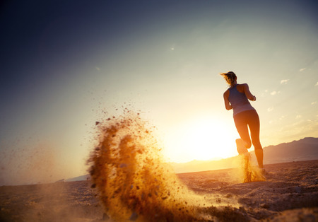 Young lady running in a desert at sunset