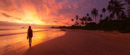 Photo pour Lady walking on the wet sandy beach during sunset - image libre de droit