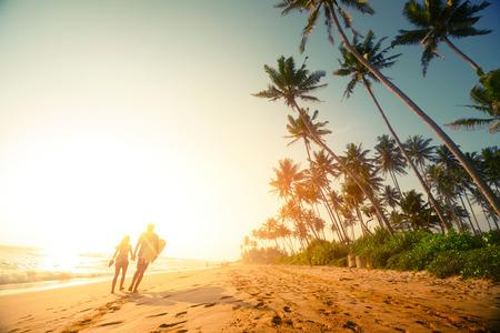 Photo pour Couple walking on the sandy beach with palm trees - image libre de droit