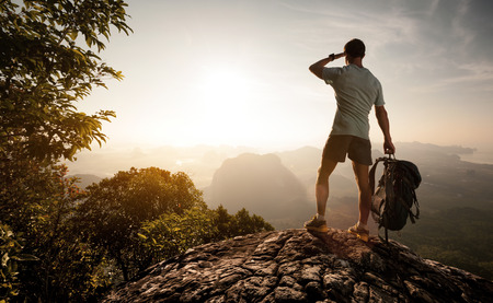 Foto de Hiker on top of the mountain enjoying sunrise over the tropical valley - Imagen libre de derechos