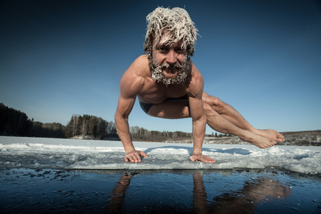 Foto de Man with frozen hair doing yoga exercise, parsva bakasana, on the ice - Imagen libre de derechos