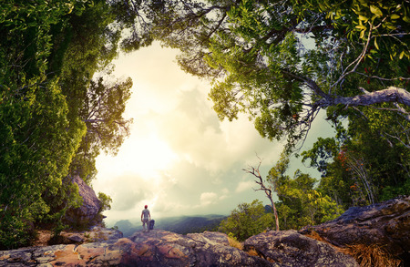 Photo pour Hiker with backpack standing on the rock surrounded by lush tropical forest - image libre de droit