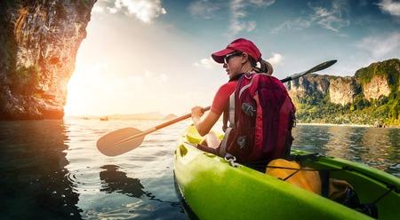 Photo pour Young lady paddling kayak - image libre de droit