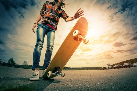 Photo for Young lady with skateboard on the road - Royalty Free Image