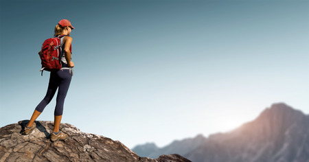Photo pour Lady hiker standing on top of the hill with clear sky and mountains on the background - image libre de droit