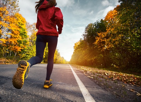 Foto de Lady running on the asphalt road through the autumn forest - Imagen libre de derechos