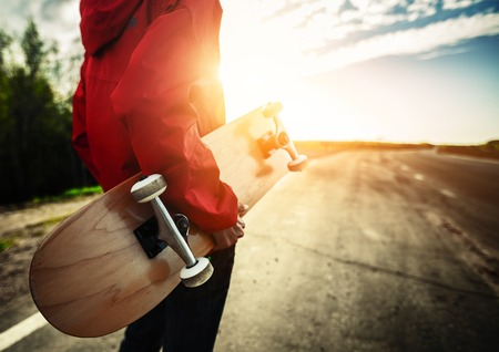 Photo pour Person with skateboard standing on the road - image libre de droit