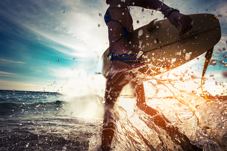 Photo pour Lady with surfboard running into the sea with lots of splashes - image libre de droit