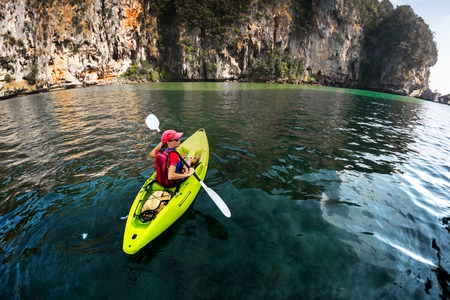 Foto de Lady paddling the kayak in the calm tropical bay - Imagen libre de derechos
