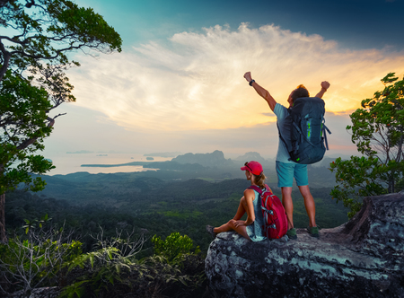 Foto de Two hikers relaxing on top of the mountain and enjoying sunset valley view - Imagen libre de derechos
