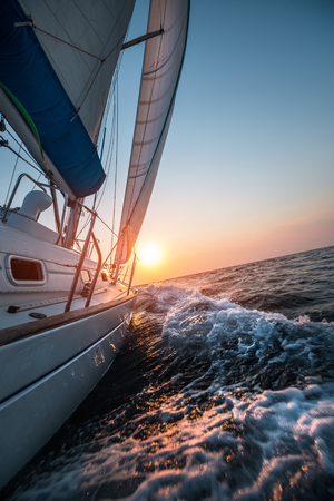 Photo pour Sail boat moving in the open sea at sunset - image libre de droit