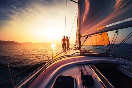 Photo pour Couple on the sailing boat at sunset - image libre de droit