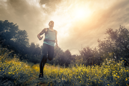 Photo pour Trail running athlete moving through the meadow - image libre de droit