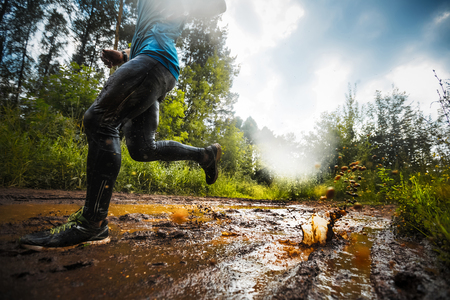 Photo pour Trial running athlete moving through the dirty puddle in the rural road - image libre de droit