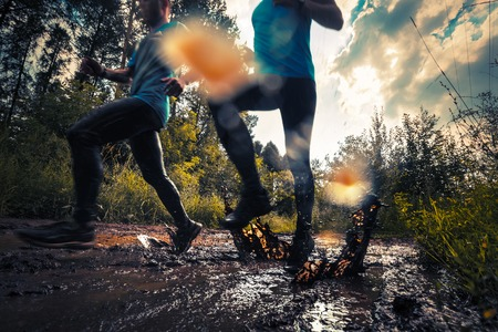 Foto de Two trail running athlete moving through the dirty puddle in the rural road - Imagen libre de derechos