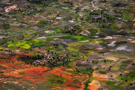 Foto de Traditional Malagasy village among red soils and green fields. Madagascar - Imagen libre de derechos