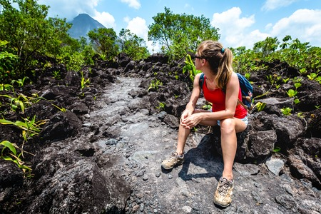 Photo pour Young woman hiker relaxing on the hard and rocky lava trail with volcano on the horizon - image libre de droit