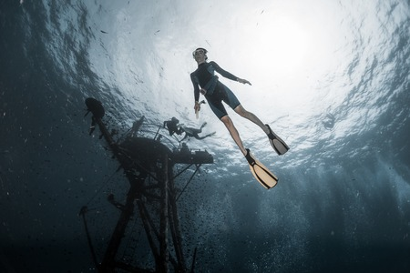 Photo for Woman freediver dives deep underwater along the ship wreck - Royalty Free Image