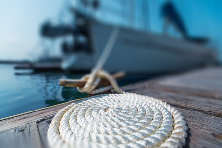 Photo pour Perfectly coiled rope on the pier with secured yachts on the background - image libre de droit