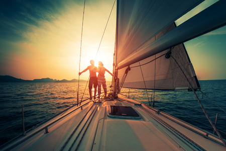 Photo pour Young couple enjoys sunset from the sailing boat moving in the tropical sea - image libre de droit