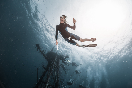 Photo for Underwater shot of woman free diver swimming near the ship wreck - Royalty Free Image