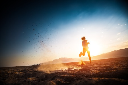 Photo pour Woman runs on the desert with lots of dust - image libre de droit