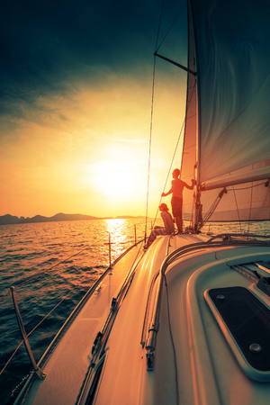 Foto de Young couple enjoys sunset from the sailing boat moving in the tropical sea - Imagen libre de derechos