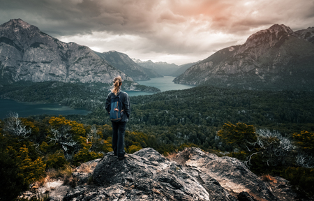 Foto de Woman hiker stands and enjoys valley view from viewpoint. Hiker reached top of the mountain and watching sunset. Patagonia, Argentina - Imagen libre de derechos