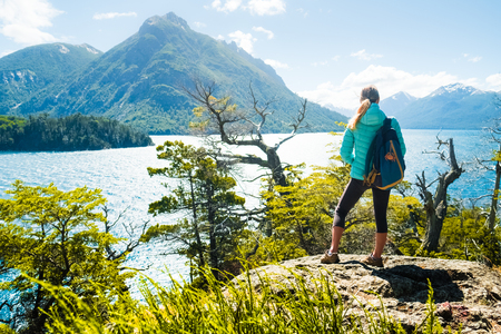 Photo pour Woman hiker stands on the coast of the lake and enjoys mountain view. Lake district of Argentina - image libre de droit