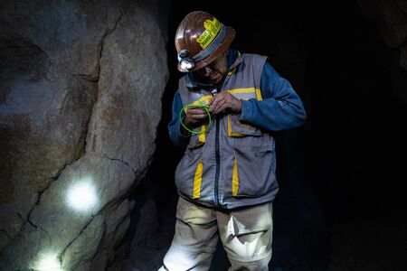 Foto de POTOSI, BOLIVIA - APRIL 02: Former miner and guide creates dynamite bomb to show its explosion for tourist group inside the mountain of Cerro Rico - Imagen libre de derechos