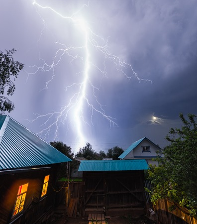 Photo pour Thunderbolt in the night sky over the village with houses and garden - image libre de droit