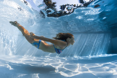 Foto de Young woman glides underwater in the pool on a sunny day - Imagen libre de derechos