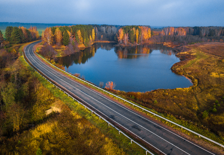 Photo for Asphalt road curves near the small lake with colorfull autumn trees on its coast - Royalty Free Image