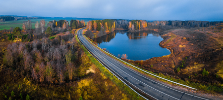 Photo for panorama of the asphalt road curving near the small lake with colorfull autumn trees on its coast - Royalty Free Image