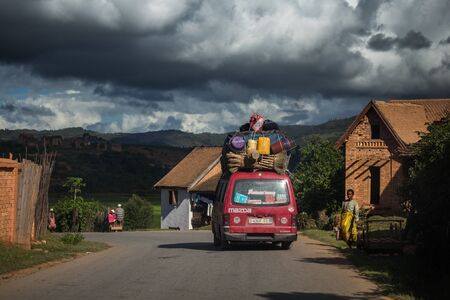 Foto de FIANARANTSOA / MADAGASCAR - 23 DECEMBER 2013: Loaded African bus moves on the paved road and passes villagers with mountains on the background - Imagen libre de derechos