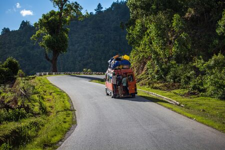 Foto de ANTSIRABE / MADAGASCAR - 23 DECEMBER 2013: Passengers hang outside the crowded and roof loaded bus with open back door moving on the spectacular curved road in mountains - Imagen libre de derechos