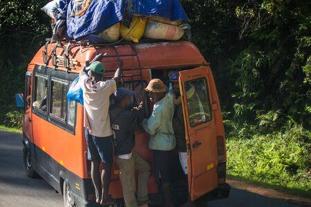 Foto de ANTSIRABE / MADAGASCAR - 23 DECEMBER 2013: Passengers hang outside the crowded loaded bus with open back door - Imagen libre de derechos