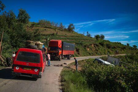 Foto de FIANARANTSOA / MADAGASCAR - 24 DECEMBER 2013: Random cars stopped on the mountain road and men help to get cargo truck out from the ditch - Imagen libre de derechos