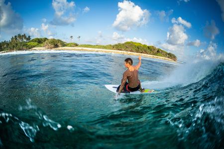 Foto de Surfer rides the ocean wave at sunset. Honkeys surf spot in the Maldives - Imagen libre de derechos