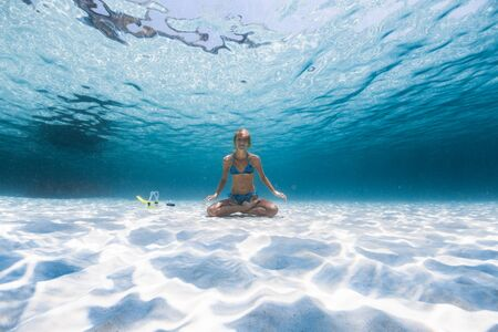 Photo for Slim yogi lady sits on the sandy sea bottom in the relaxed Lotus pose, smiles and looks at the camera - Royalty Free Image