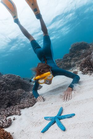 Photo for Woman snorkeling and skin diving in the tropical sea and gets closer to the blue starfish lying on the sandy bottom. Focus on the model's face - Royalty Free Image