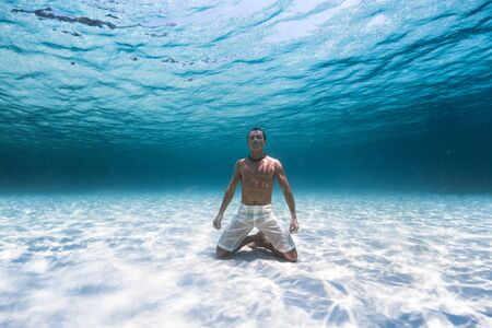 Photo for Young muscular man stands on the knees on the sandy sea bottom in a relaxed pose - Royalty Free Image