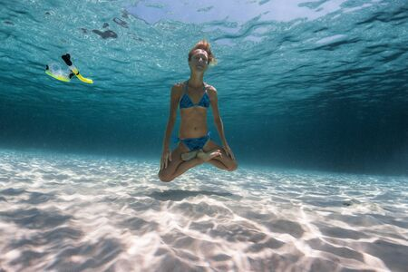 Photo for Slim yogi lady holds the breath underwater and hovers over the bottom in the Lotus pose with mask and snorkel floating around - Royalty Free Image