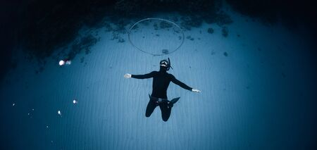 Photo for Freediver hangs deep underwater over the sandy bottom and blows the huge ring bubble - Royalty Free Image