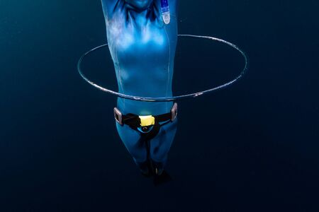 Photo for Woman freediver glides underwater throught the ring bubble - Royalty Free Image