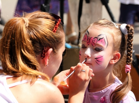 Foto de artist paints butterfly on face of cute little girl - Imagen libre de derechos