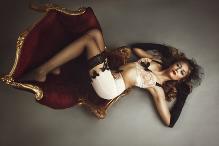 Photo pour Young beautiful woman lying on chair - retro style - image libre de droit